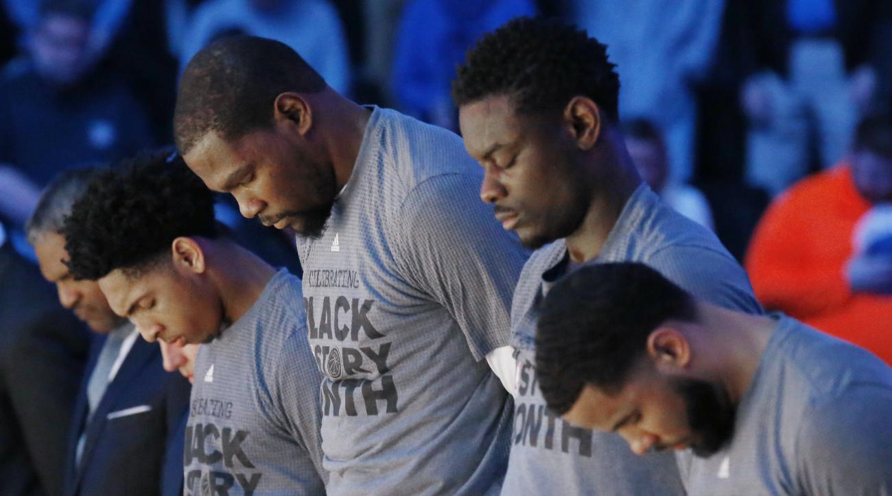 Oklahoma Thunder players, from left, Cameron Payne, Kevin Durant, Andrew Morrow and D.J. Augustin bow their heads during a moment of silence for Ingrid Williams, the wife of Thunder assistant coach Monty Williams, who died Wednesday as the result of a car