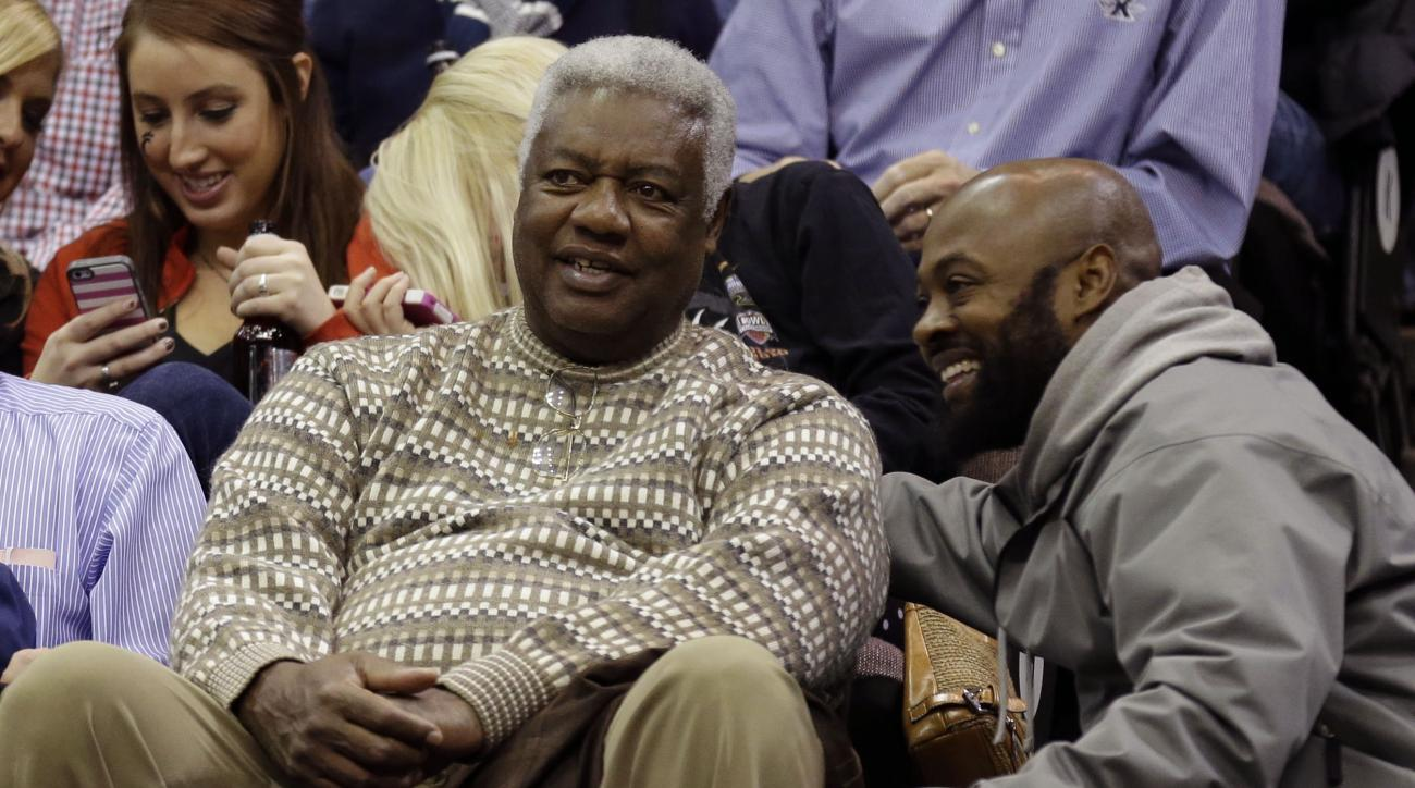 FILE - In this Saturday, Dec. 14, 2013 file photo, Former NBA great Oscar Robertson, left, talks with a friend in the first half of an NCAA college basketball game between Xavier and Cincinnati in Cincinnati. Hall of Famer Oscar Robertson receives a Lifet