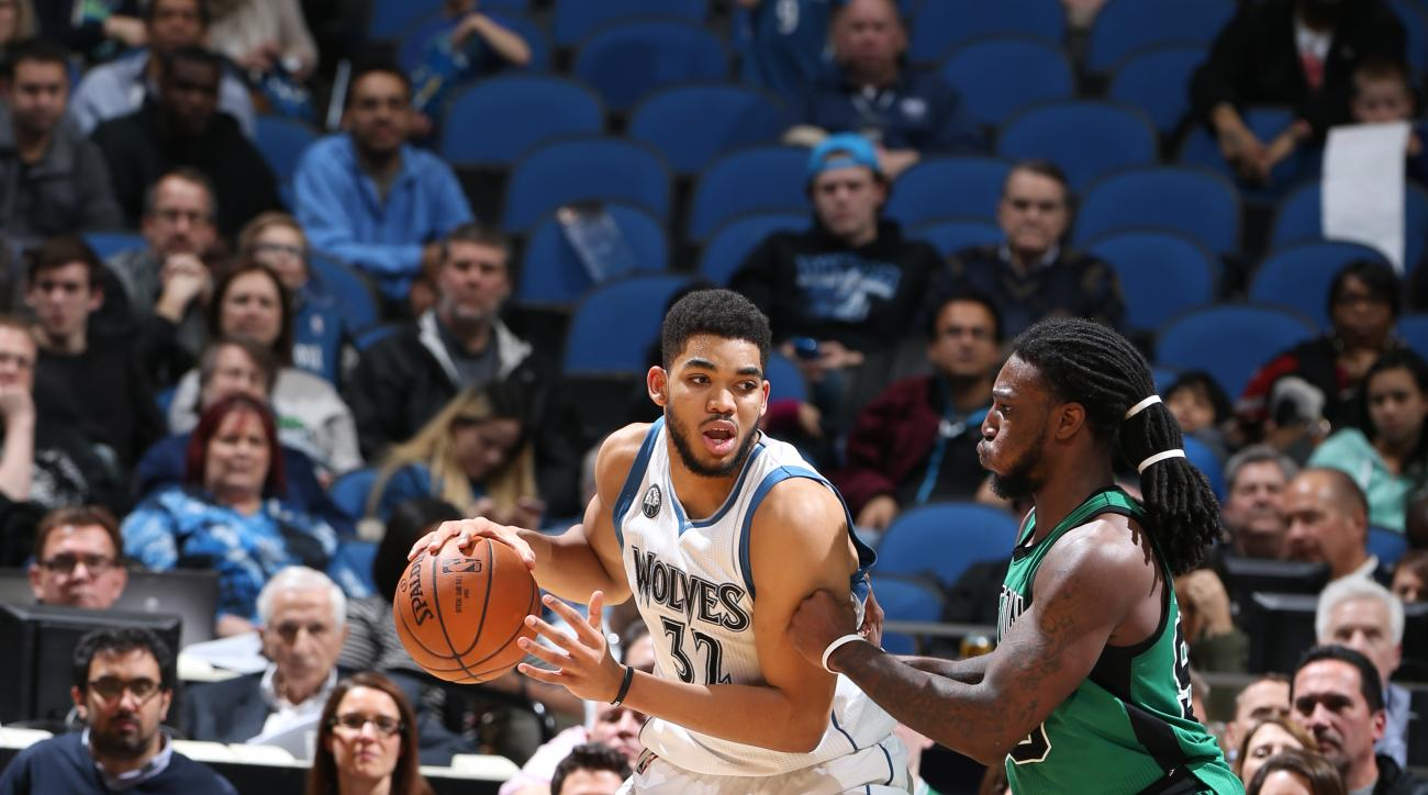 MINNEAPOLIS, MN - FEBRUARY 22:  Karl-Anthony Towns #32 of the Minnesota Timberwolves handles the ball against Jae Crowder #99 of the Boston Celtics on February 22, 2016 at Target Center in Minneapolis, Minnesota. (Photo by David Sherman/NBAE via Getty Ima