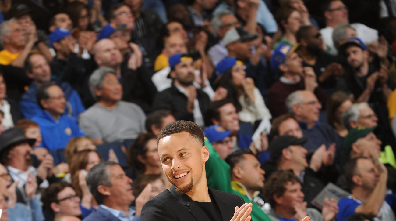 OAKLAND, CA - MARCH 1: Stephen Curry #30 of the Golden State Warriors cheers on his team as they face the Atlanta Hawks on March 1, 2016 at Oracle Arena in Oakland, California. (Photo by Noah Graham/NBAE via Getty Images)
