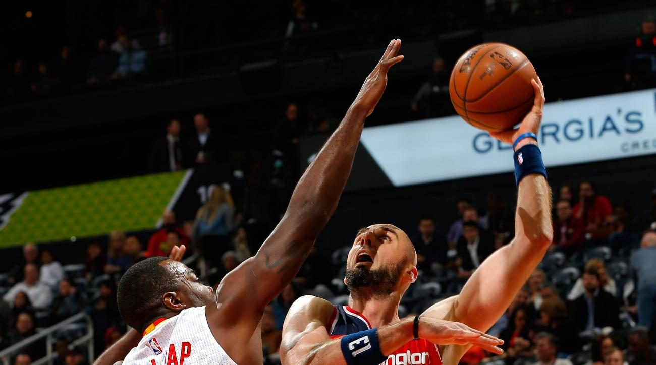 ATLANTA, GA - MARCH 21:  Marcin Gortat #13 of the Washington Wizards attempts a shot against Paul Millsap #4 of the Atlanta Hawks at Philips Arena on March 21, 2016 in Atlanta, Georgia.  NOTE TO USER User expressly acknowledges and agrees that, by downloa