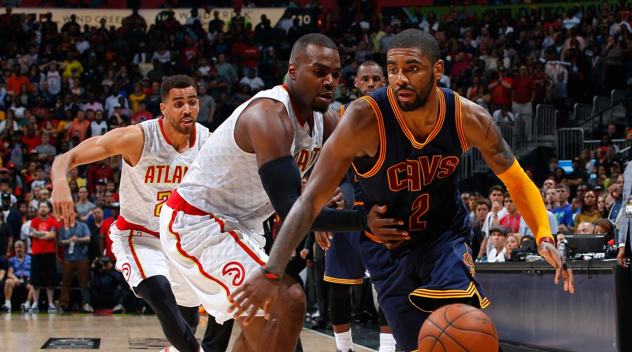 ATLANTA, GEORGIA - APRIL 01:  Kyrie Irving #2 of the Cleveland Cavaliers drives around Paul Millsap #4 of the Atlanta Hawks at Philips Arena on April 1, 2016 in Atlanta, Georgia.  NOTE TO USER User expressly acknowledges and agrees that, by downloading an