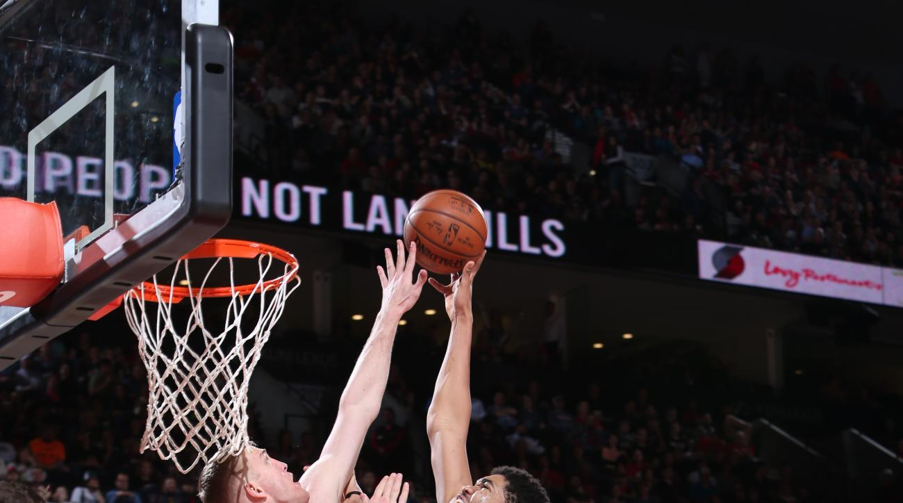PORTLAND, OR - APRIL 9:  Karl-Anthony Towns #32 of the Minnesota Timberwolves goes to the basket against Mason Plumlee #24 of the Portland Trail Blazers on April 9, 2016 at the Moda Center in Portland, Oregon. (Photo by Sam Forencich/NBAE via Getty Images