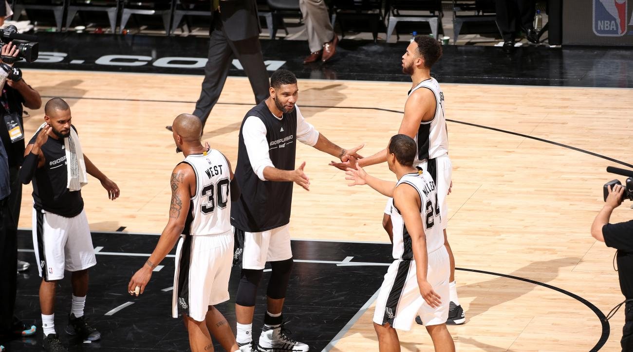 SAN ANTONIO, TX - APRIL 19: Tim Duncan #21 of the San Antonio Spurs high fives his teammates Andre Miller #24 and Kyle Anderson #1 of the San Antonio Spurs during the game against the Memphis Grizzlies in Game Two of the Western Conference Quarterfinals d