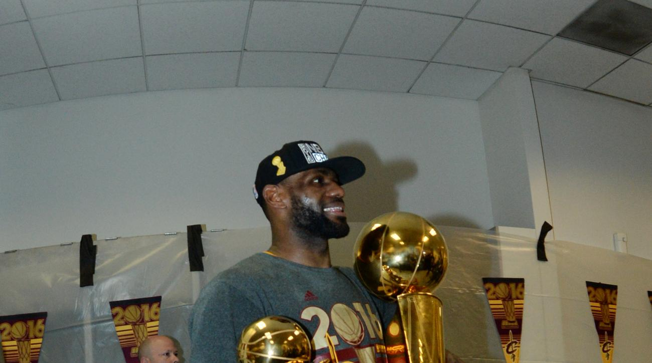 OAKLAND, CA - JUNE 19:  LeBron James #23 of the Cleveland Cavaliers celebrates with the Larry O'Brien NBA Championship Trophy and the Bill Russell NBA Finals Most Valuable Player Award after winning Game Seven of the 2016 NBA Finals against the Golden Sta