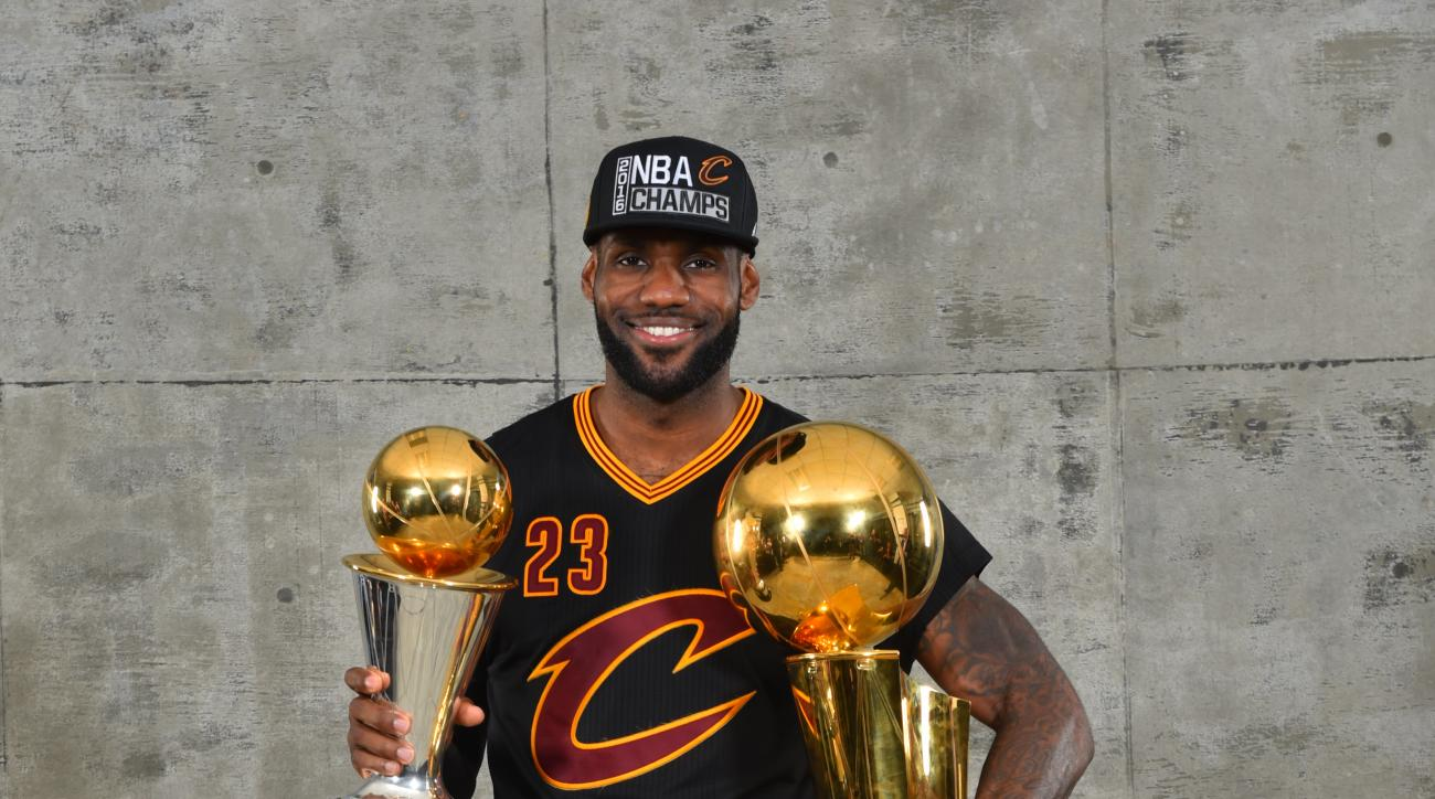 OAKLAND, CA - JUNE 19:  LeBron James #23 of the Cleveland Cavaliers poses for a portrait with his MVP Trophy and the World Championship Trophy after winning the NBA Championship against the Golden State Warriors during the 2016 NBA Finals Game Seven on Ju