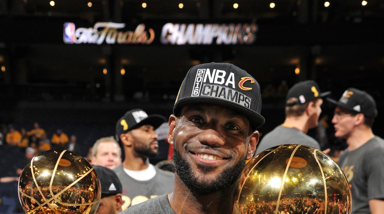 OAKLAND, CA - JUNE 19:  LeBron James #23 of the Cleveland Cavaliers celebrates with the Bill Russell NBA Finals Most Valuable Player Award and the Larry O'Brien NBA Championship Trophy after winning Game Seven of the 2016 NBA Finals against the Golden Sta