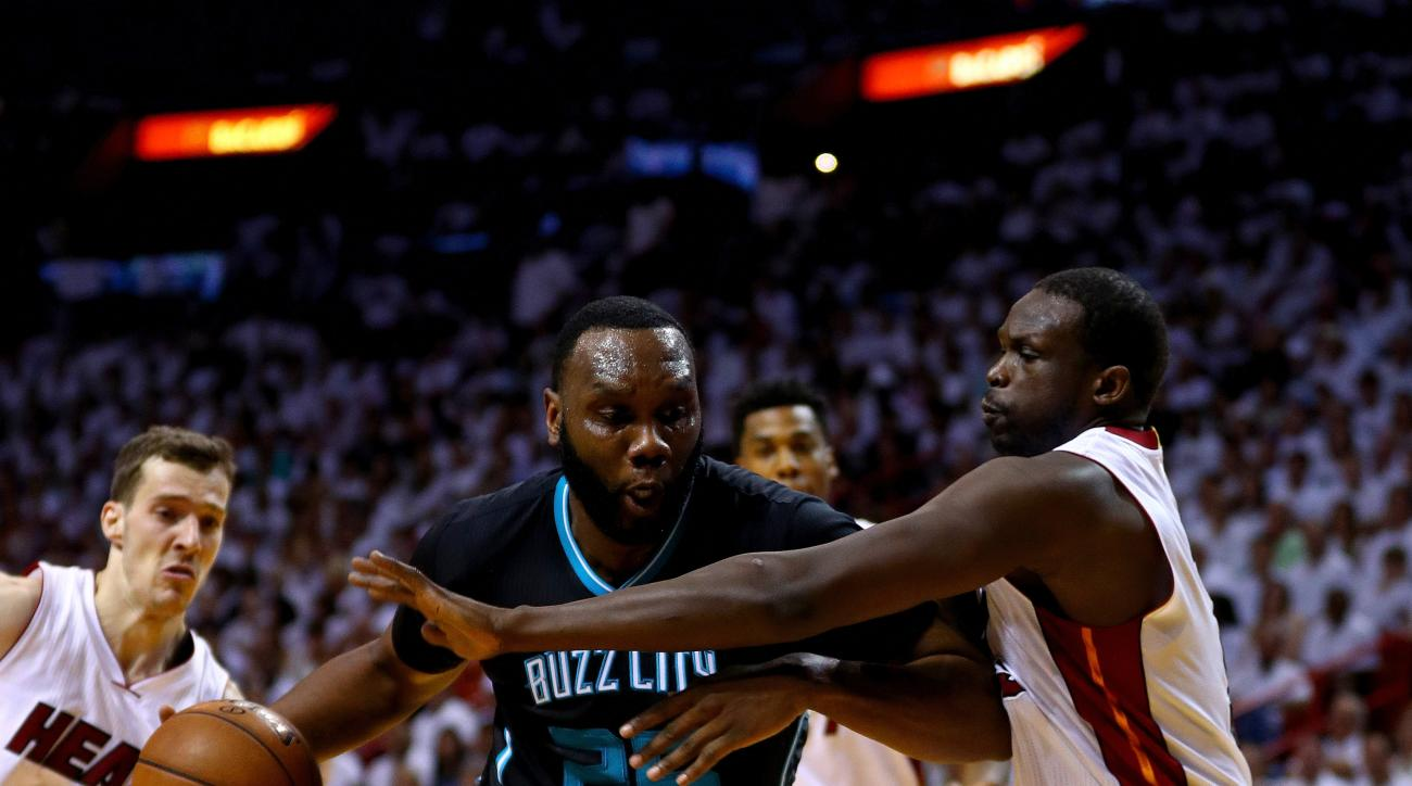 MIAMI, FL - MAY 01:  Al Jefferson #25 of the Charlotte Hornets drives on Luol Deng #9 of the Miami Heat during Game Seven of the Eastern Conference Quarterfinals of the 2016 NBA Playoffs at American Airlines Arena on May 1, 2016 in Miami, Florida. (Photo