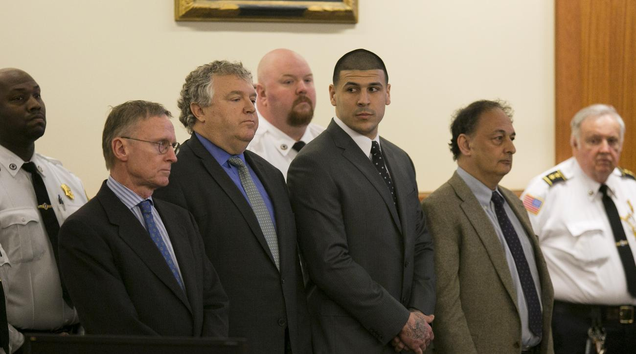 Former New England Patriots NFL football player Aaron Hernandez, center, stands with his defense attorneys, from left, Charles Rankin, Micheal Fee and James Sultan, as the verdict is read in his murder trial, Wednesday, April 15, 2015, at Bristol County S
