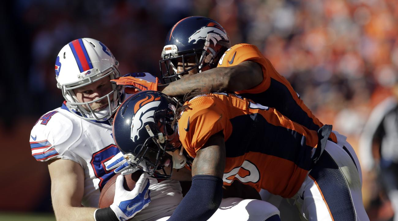 FILE - In this Dec. 7, 2014, file photo, Buffalo Bills tight end Scott Chandler, left, is tackled by Denver Broncos strong safety David Bruton, right foreground, and cornerback Aqib Talib during the first half in an NFL football game in Denver. Bruton aim