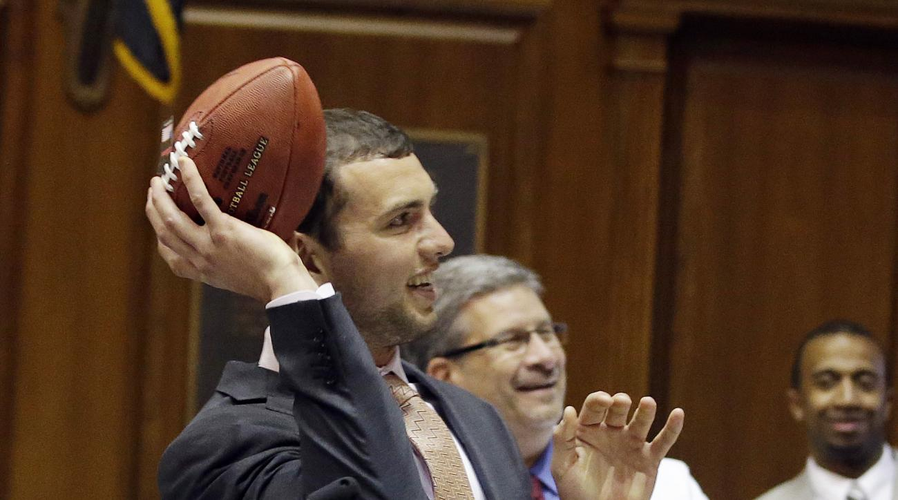 Indianapolis Colts quarterback Andrew Luck throws a pass to Speaker of the House Brian Bosma, R-Indianapolis, after Luck spoke to the House of Representatives at the Statehouse, Tuesday, April 21, 2015, in Indianapolis. Luck and experts from Riley Hospita