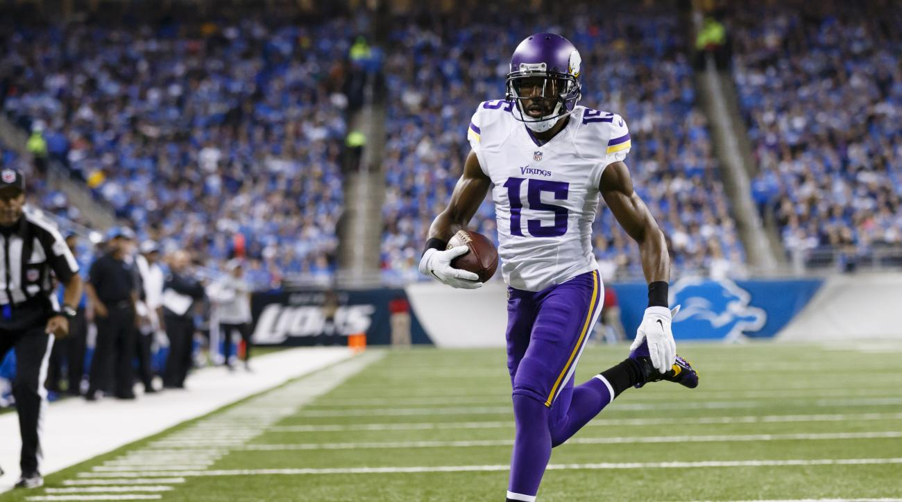 Minnesota Vikings wide receiver Greg Jennings (15) runs the ball for a touchdown against the Detroit Lions during an NFL football game at Ford Field in Detroit, Sunday, Dec. 14, 2014. (AP Photo/Rick Osentoski)