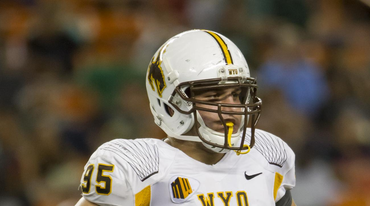 FILE - In this Oct. 11, 2014, file photo, Wyoming defensive tackle Patrick Mertens looks on during a break between plays in the second quarter of an NCAA college football game against Hawaii in Honolulu. In 2011, he contracted West Nile virus, pneumonia a