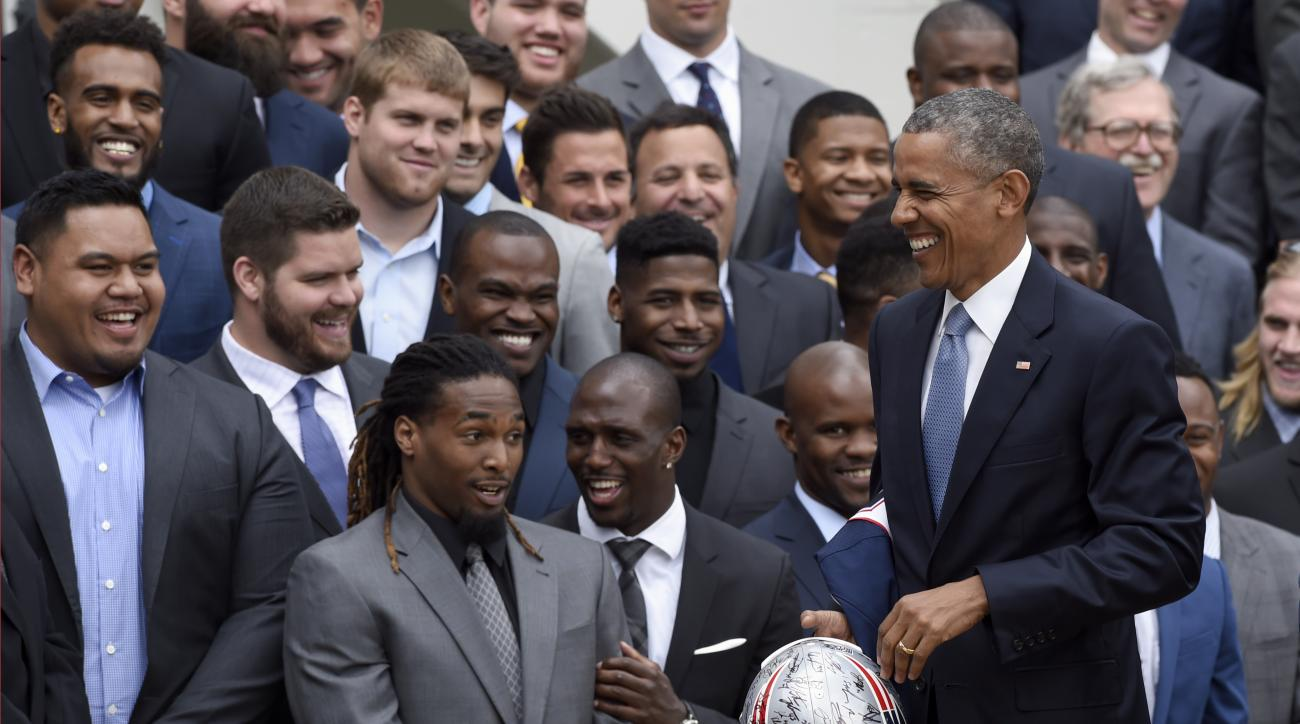 President Barack Obama holds a signed New England Patriots football helmet during a ceremony on the South Lawn of the White House in Washington, Thursday, April 23, 2015, to honor the Super Bowl Champion New England Patriots for their Super Bowl XLIX vict