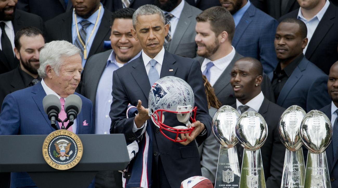 President Barack Obama looks over a signed New England Patriots football helmet presented to him by New England Patriots owner Robert Kraft, left, during a ceremony on the South Lawn of the White House in Wasington, Thursday, April 23, 2015, where the pre