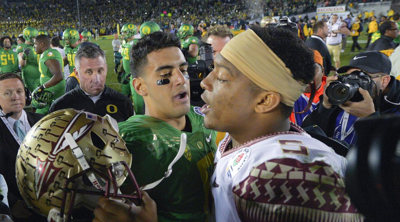 FILE - In this Jan. 1, 2015, file photo, Oregon quarterback Marcus Mariota, center left, greets Florida State quarterback Jameis Winston after Oregon's win in the Rose Bowl NCAA college football playoff semifinal game in Pasadena, Calif. There will be sev