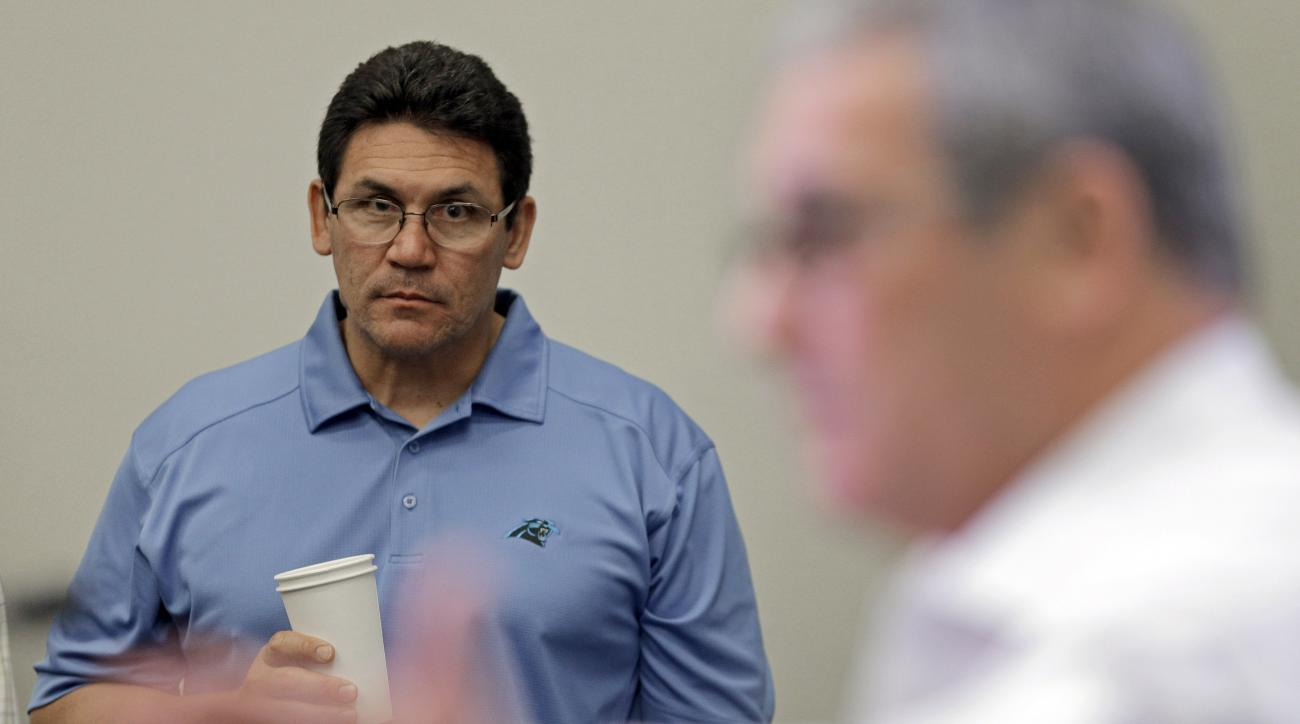 Carolina Panthers head coach Ron Rivera, back, looks on as general manager Dave Gettleman, right, answers a question during a pre-draft news conference for the NFL football team in Charlotte, N.C., Tuesday, April 28, 2015. (AP Photo/Chuck Burton)