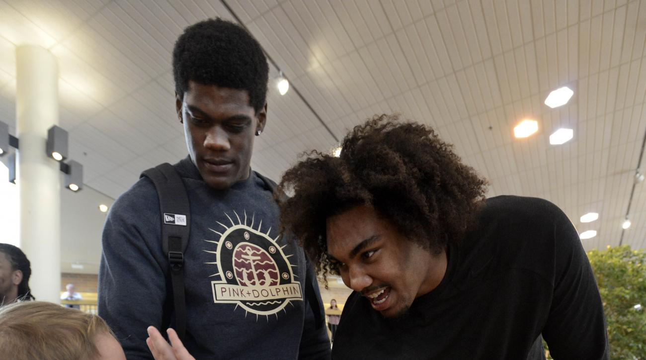 NFL prospect Leonard Williams of USC, right, greets pediatric patient Dylan Poznan left, while fellow prospect Randy Gregory of Nebraska, center, looks on before NFL PLAY 60 activities at Shriners Hospital for Children Thursday, April 30, 2015, in Chicago