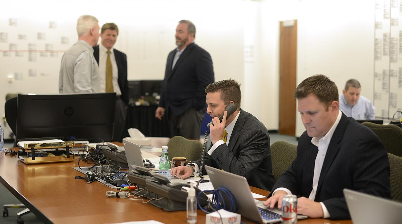 Green Bay Packers director of player personnel Eliot Wolf, second from right, talks on the phone as general manager Ted Thompson, president Mark Murphy and head coach Mike McCarthy visit with each other inside the war room during the NFL Draft at Lambeau