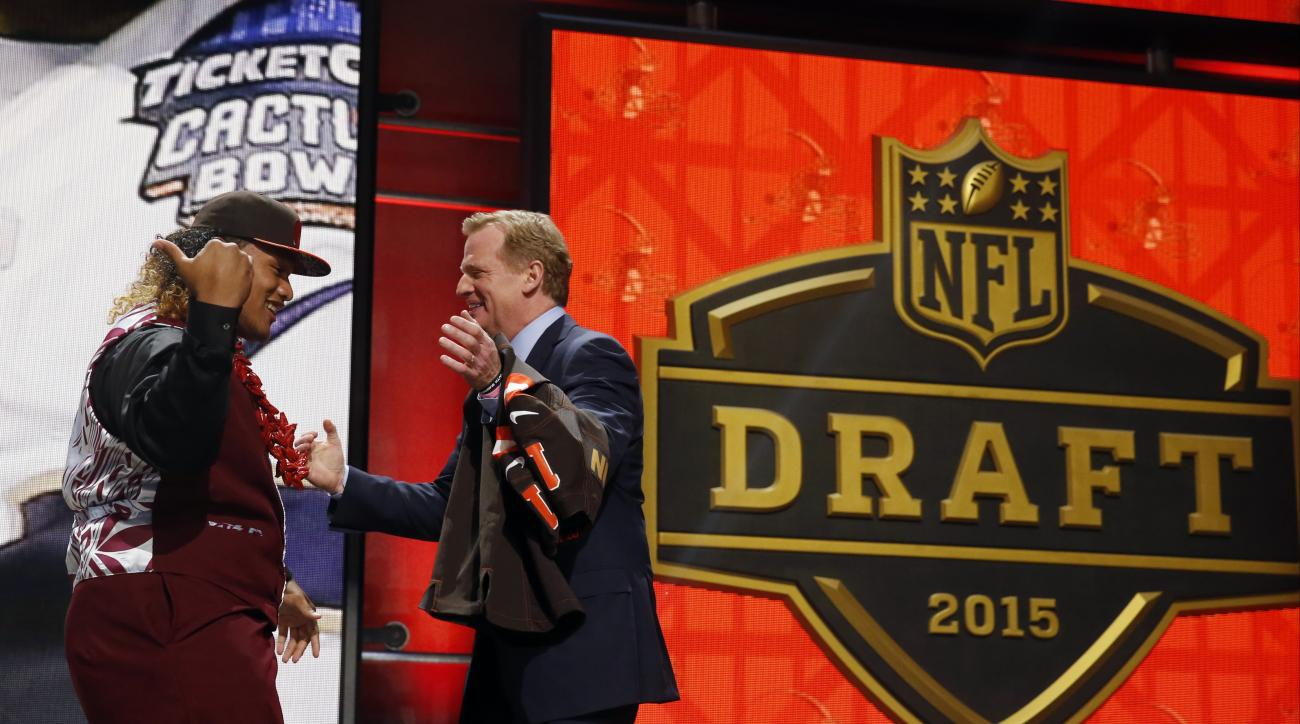 Washington defensive lineman Danny Shelton celebrates with NFL commissioner Roger Goodell after being selected by the Cleveland Browns as the 12th pick in the first round of the 2015 NFL Draft,  Thursday, April 30, 2015, in Chicago. (AP Photo/Charles Rex