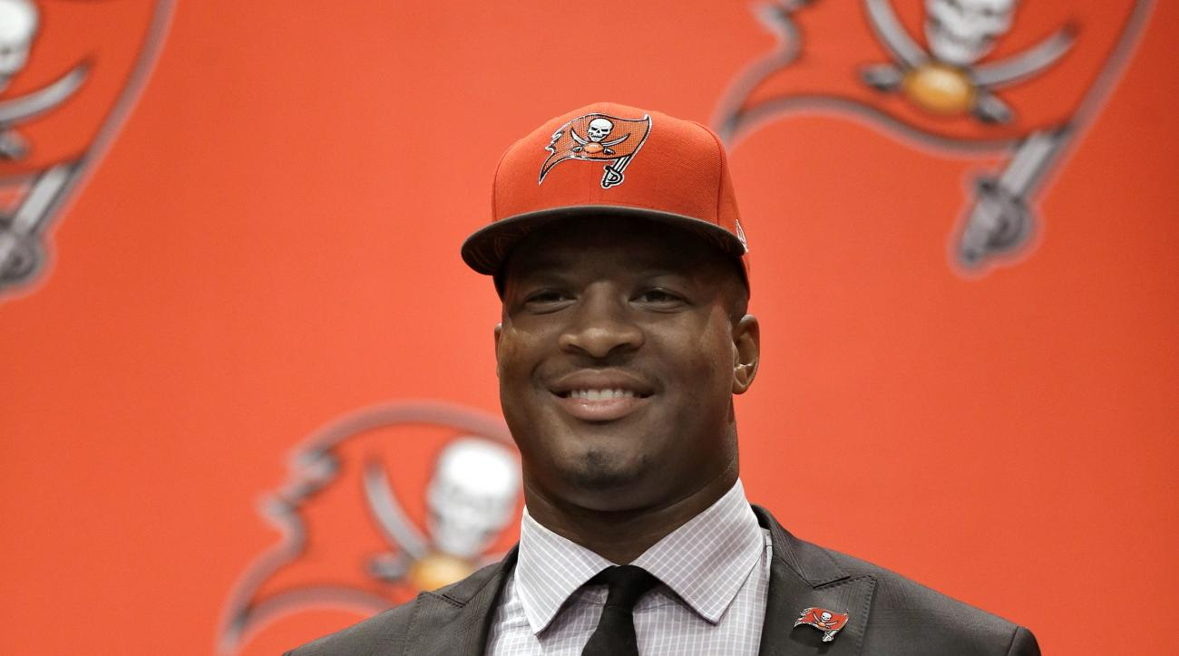 Tampa Bay Buccaneers first-round draft pick Jameis Winston holds up his jersey during a news conference Friday, May 1, 2015, in Tampa, Fla. Winston, a former Florida State quarterback, was the first overall pick. (AP Photo/Chris O'Meara)