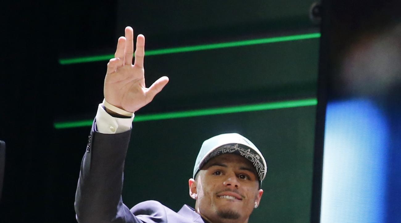 Ohio State wide receiver Devin Smith celebrates after being selected by the New York Jets as the 37th pick in the second round of the 2015 NFL Football Draft,  Friday, May 1, 2015, in Chicago. (AP Photo/Charles Rex Arbogast)