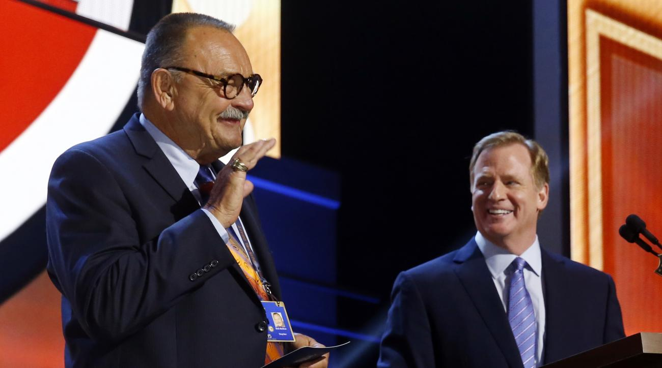 NFL Hall of Famer Dick Butkus, left, waves as NFL commissioner Roger Goodell introduces him before Butkus announces that the Chicago Bears selects Florida State defensive lineman Eddie Goldman as the 39th pick in the second round of the 2015 NFL Football
