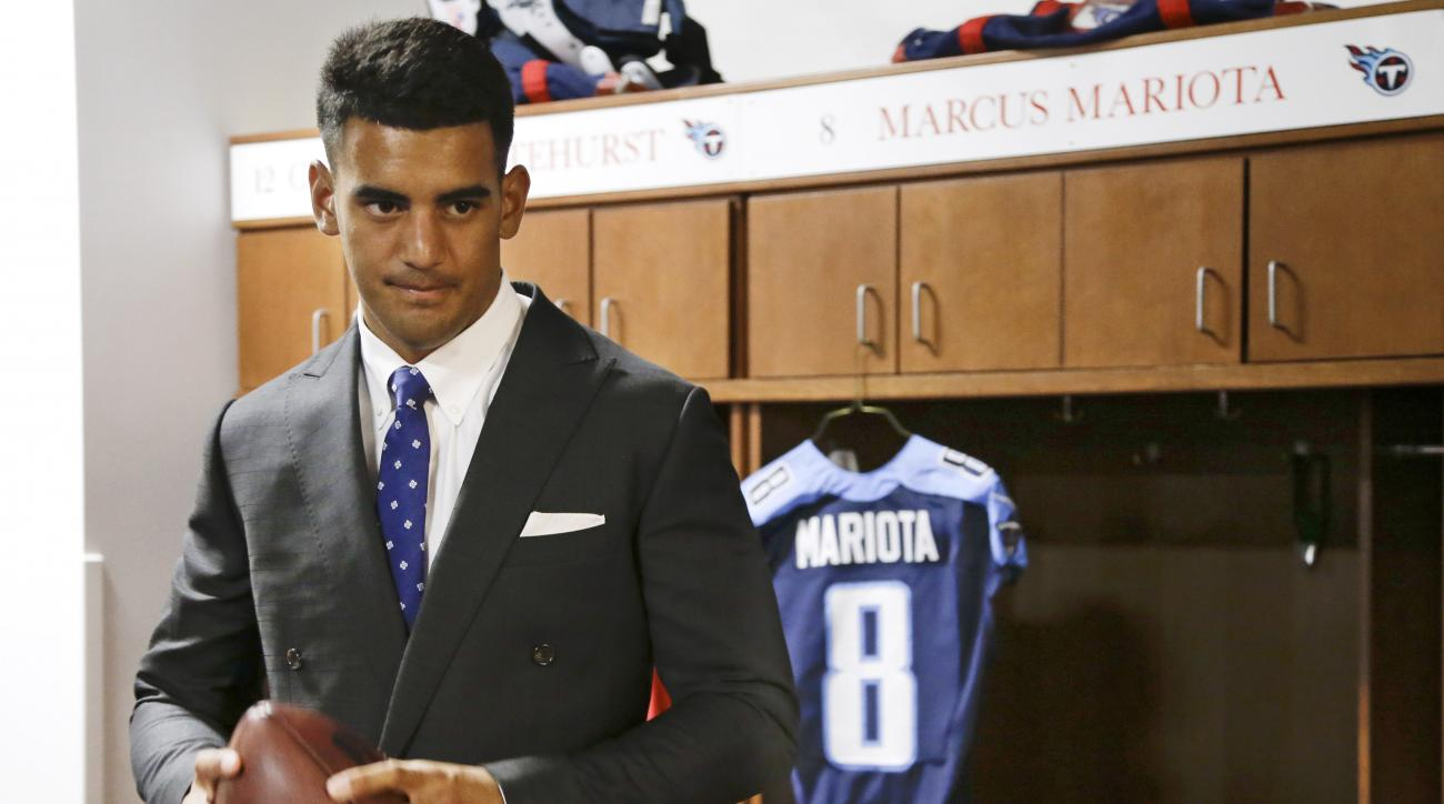 Marcus Mariota, former Oregon quarterback and overall No. 2 NFL football draft pick by the Tennessee Titans, poses for photos in the locker room Friday, May 1, 2015, in Nashville, Tenn. Mariota was selected by the Titans in the first round Thursday. (AP P