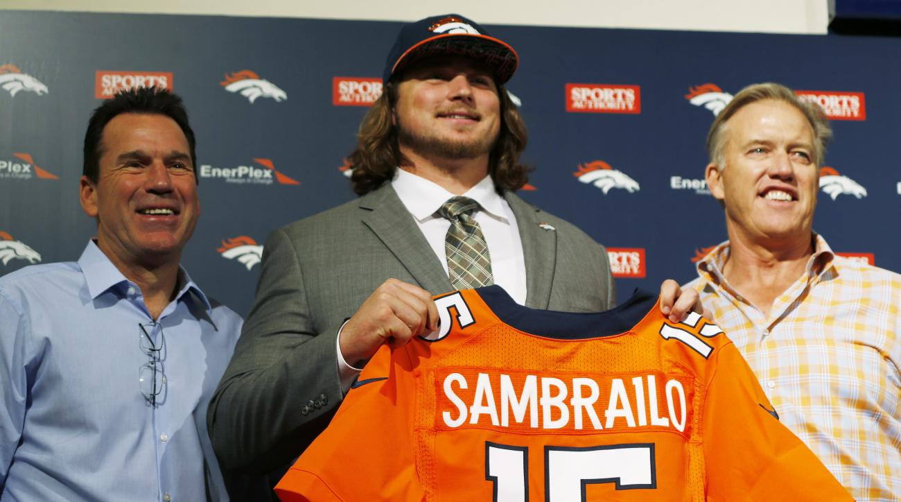 Former Colorado State offensive lineman Ty Sambrailo, center, the Denver Broncos second-round pick in the NFL Draft, shows off his new jersey with head coach Gary Kubiak, left, and general manager John Elway during an NFL football news conference Saturday