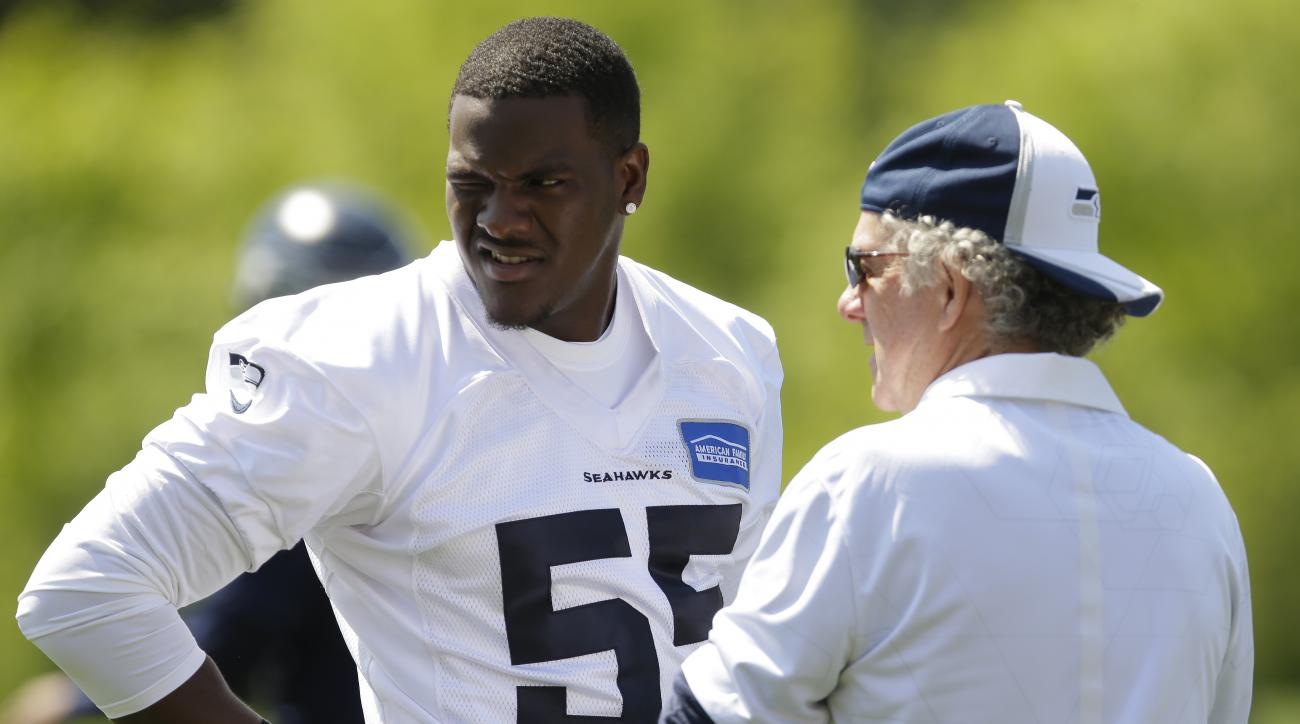 Seattle Seahawks rookie defensive end Frank Clark (55) talks with quarterbacks coach Carl Smith, right, during NFL football rookie minicamp, Friday, May 8, 2015, in Renton, Wash. (AP Photo/Ted S. Warren)