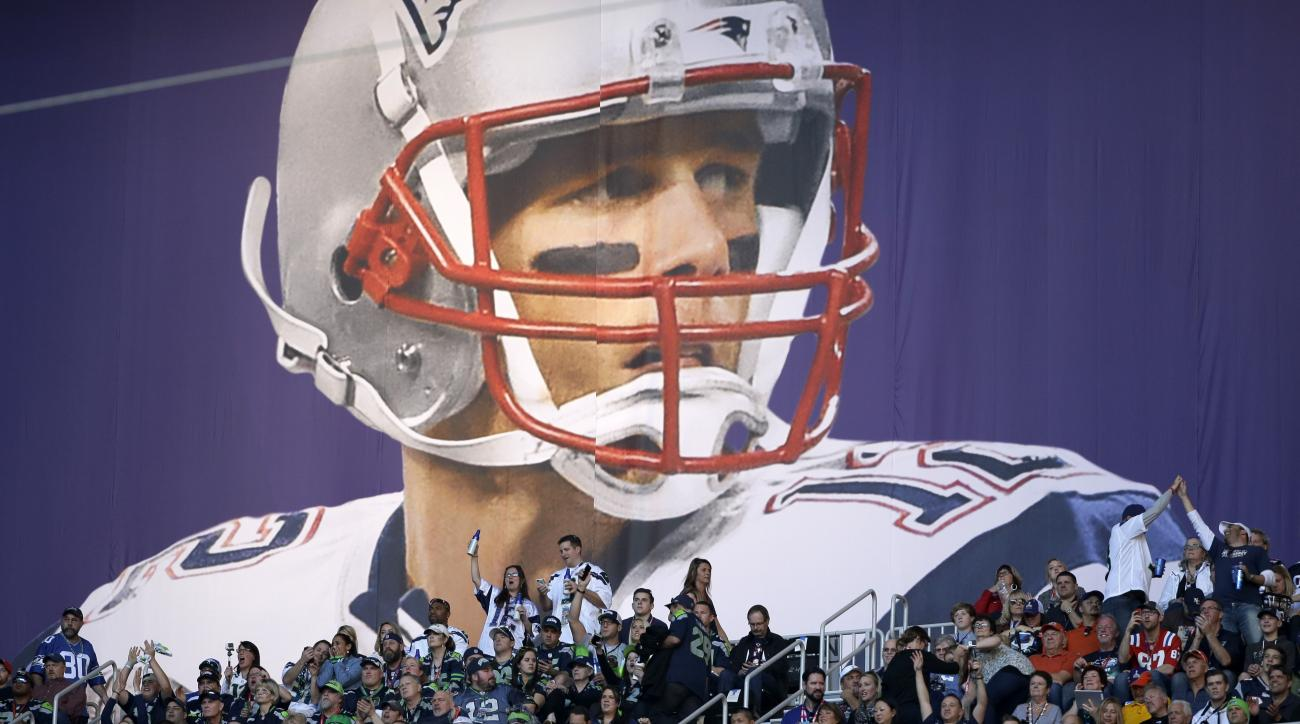 Fans cheer under a banner of New England Patriots quarterback Tom Brady (12) before the NFL Super Bowl XLIX football game between the Seattle Seahawks and the New England Patriots Sunday, Feb. 1, 2015, in Glendale, Ariz. (AP Photo/Matt Slocum)