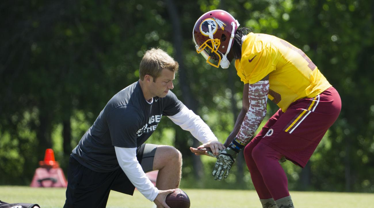 Washington Redskins offensive coordinator Sean McVay, left, works with quarterback Robert Griffin III during an NFL football organized team activity at Redskins Park, on Tuesday, May 26, 2015, in Ashburn, Va. (AP Photo/Evan Vucci)