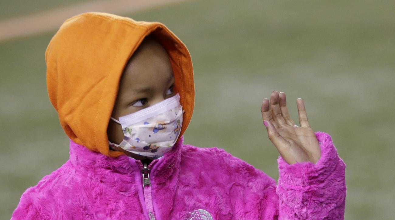 FILE - In this Nov. 6, 2014 file photo, Leah Still waves during a ceremony in the first half of an NFL football game between the Cincinnati Bengals and the Cleveland Browns in Cincinnati.  Bengals defensive tackle Devon Still is asking for prayers for his