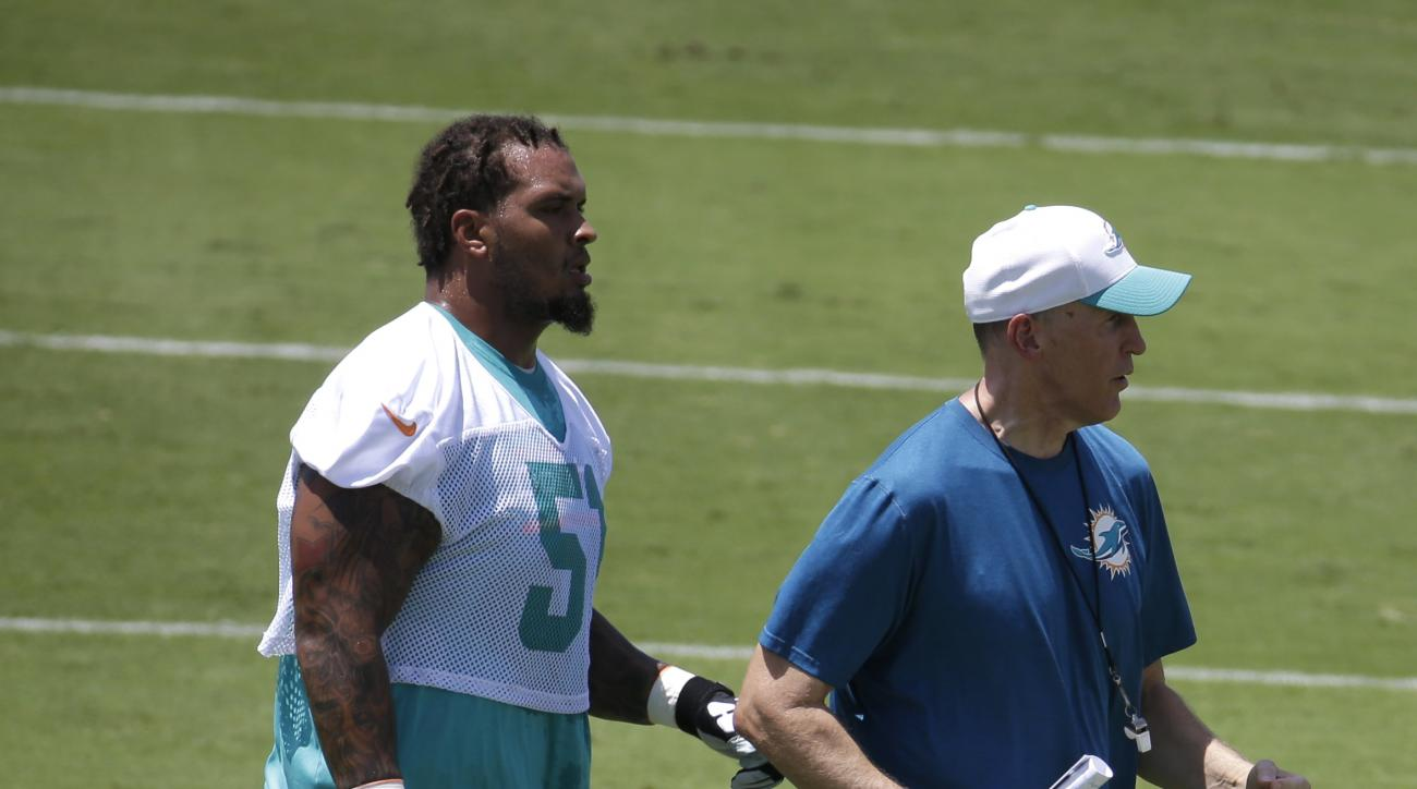 Miami Dolphins guard Mike Pouncey (51) walks on the field with head coach Joe Philbin, right, during an NFL football organized team activity, Monday, June 1, 2015, in Davie, Fla. (AP Photo/Lynne Sladky)