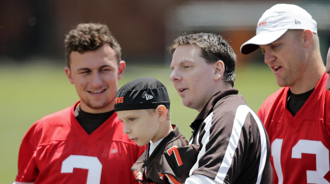 Cleveland Browns quarterbacks Johnny Manziel (2) and Josh McCown (13) spend time with Dylan Sutcliffe, 9, and his dad, Derek, during an NFL football organized team activity, Tuesday, June 2, 2015, in Berea, Ohio. Sutcliffe signed a contract with the Brown