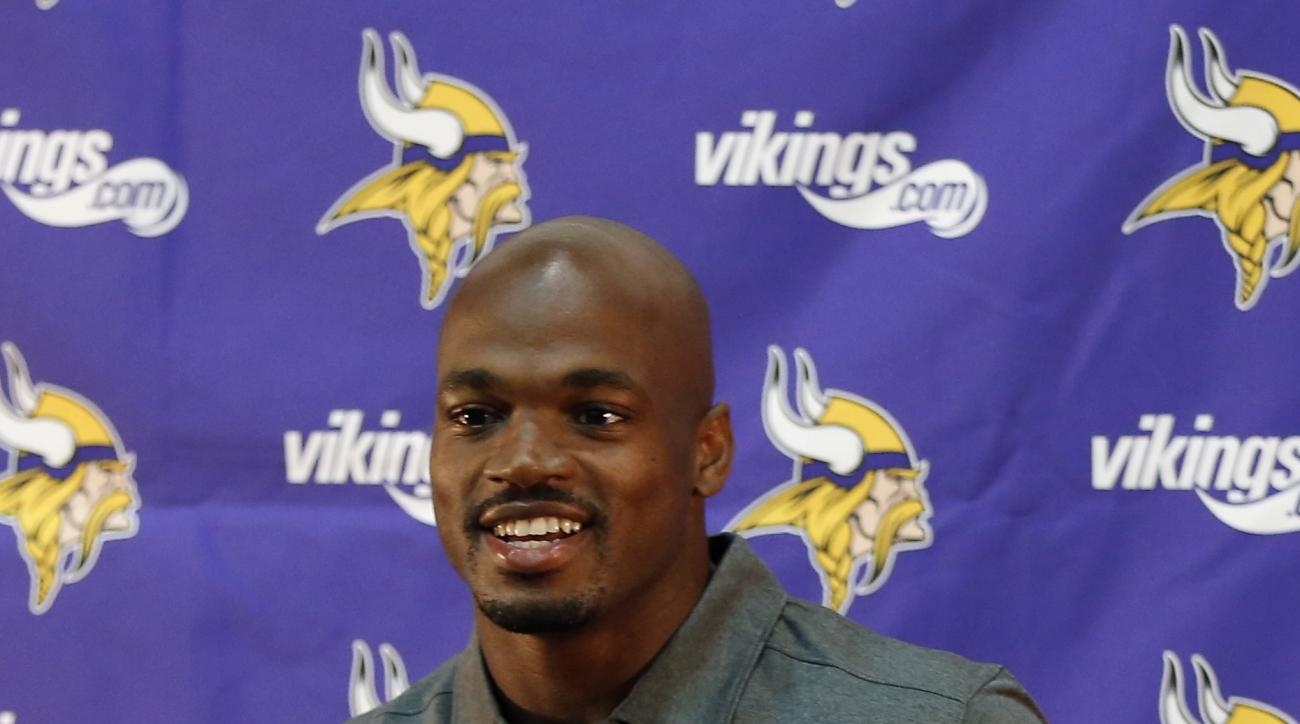Minnesota Vikings running back Adrian Peterson greets the media at the team's NFL football Winter Park headquarters, Tuesday, June 2, 2015 in Eden Prairie, Minn., after he took part in voluntary practice after nine months away. Peterson missed the final 1
