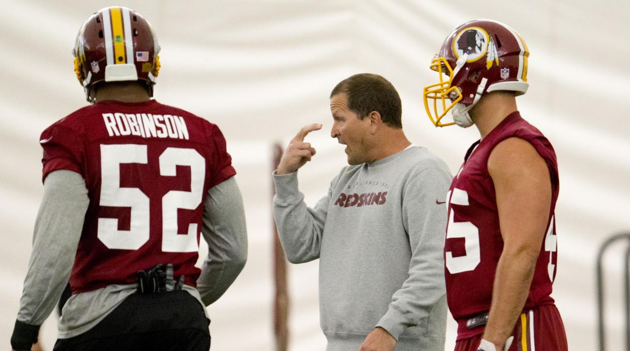 Washington Redskins defensive coordinator Joe Barry, center, works with linebackers Keenan Robinson, left, and Houston Bates, right, during an NFL football organized team activity at Redskins Park, Wednesday, June 3, 2015, in Ashburn, Va. (AP Photo/Pablo