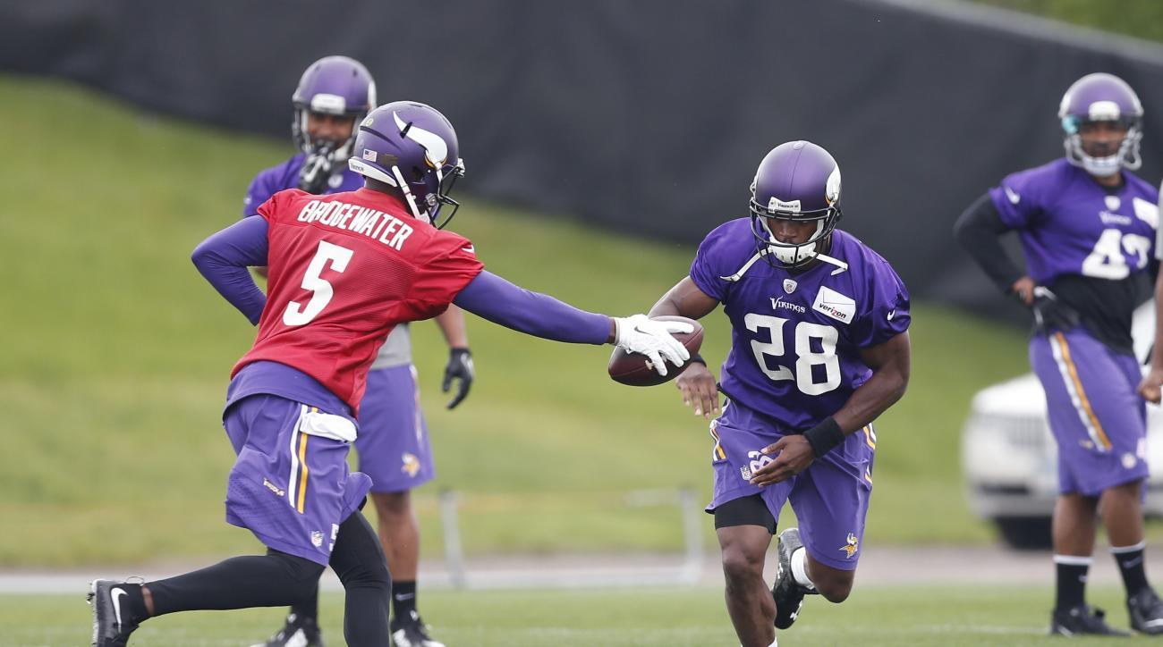 Minnesota Vikings quarterback Teddy Bridgewater, left, makes a fake handoff to running back Adrian Peterson during an NFL football team practice, Thursday, June 4, 2015, in Eden Prairie, Minn. (AP Photo/Jim Mone)