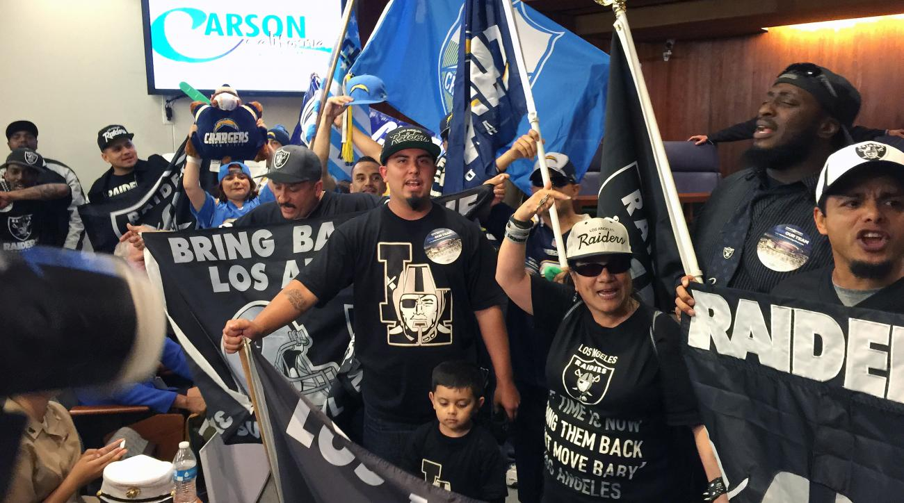 "In this photo taken Tuesday, April 21, 2015, football fans, who want to see an NFL team return to the Los Angeles area after two decades, chant "" bring them back!"" before a Carson City Council vote on whether to approve the plan to build an NFL football s"