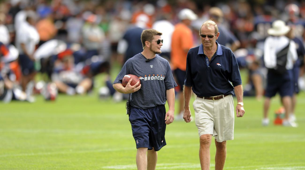 Denver Broncos owner Pat Bowlen, right, talks with his son John Bowlen during NFL football training camp in Englewood, Colo., on Friday, July 29, 2011. (AP Photo/Jack Dempsey)