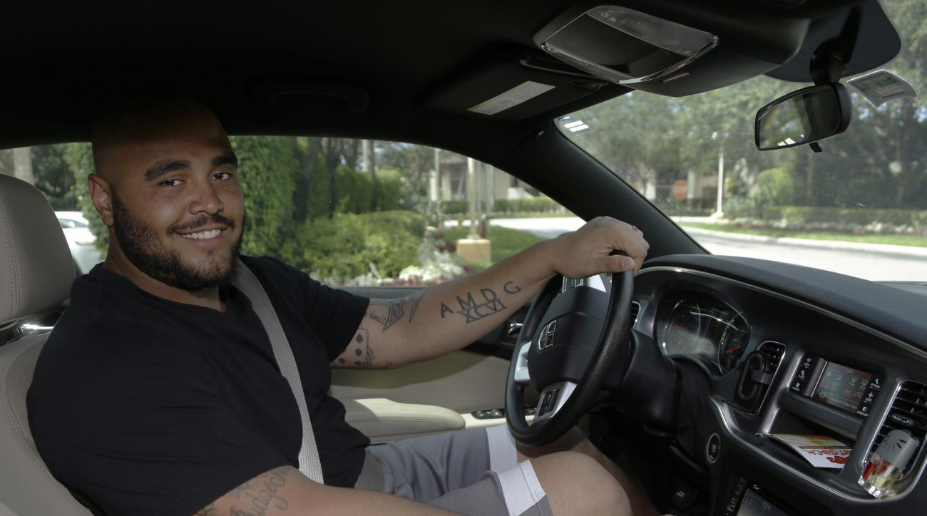 Miami Dolphins defensive lineman A.J. Francis poses inside his vehicle after an NFL football organized team activity, Monday, June 8, 2015, in Davie, Fla. Francis wants to help the Dolphins make the playoffs, but this offseason he has other destinations i