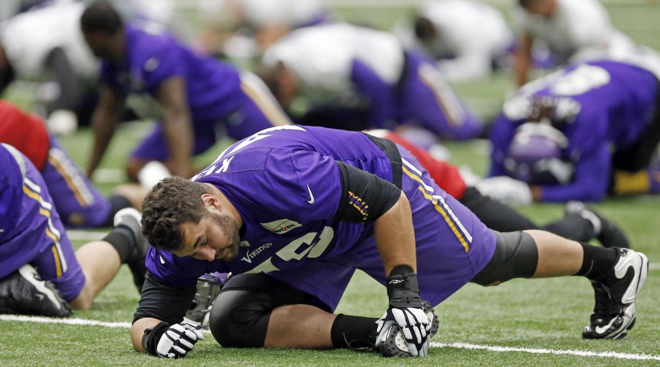 Minnesota Vikings tackle Matt Kalil (75) stretches during NFL football practice, Thursday, June 11, 2015, in Eden Prairie, Minn.  (AP Photo/Jim Mone)