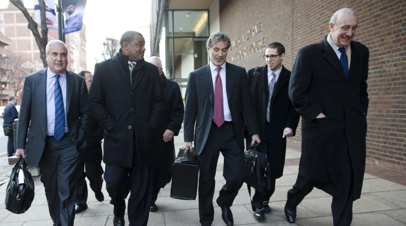 FILE - In this Nov. 19, 2014, file photo, co-lead players' lawyer Christopher Seeger, center right, and client former NFL player Shawn Wooden, center left, speak with members of the media after a hearing on the proposed NFL concussion settlement outside o