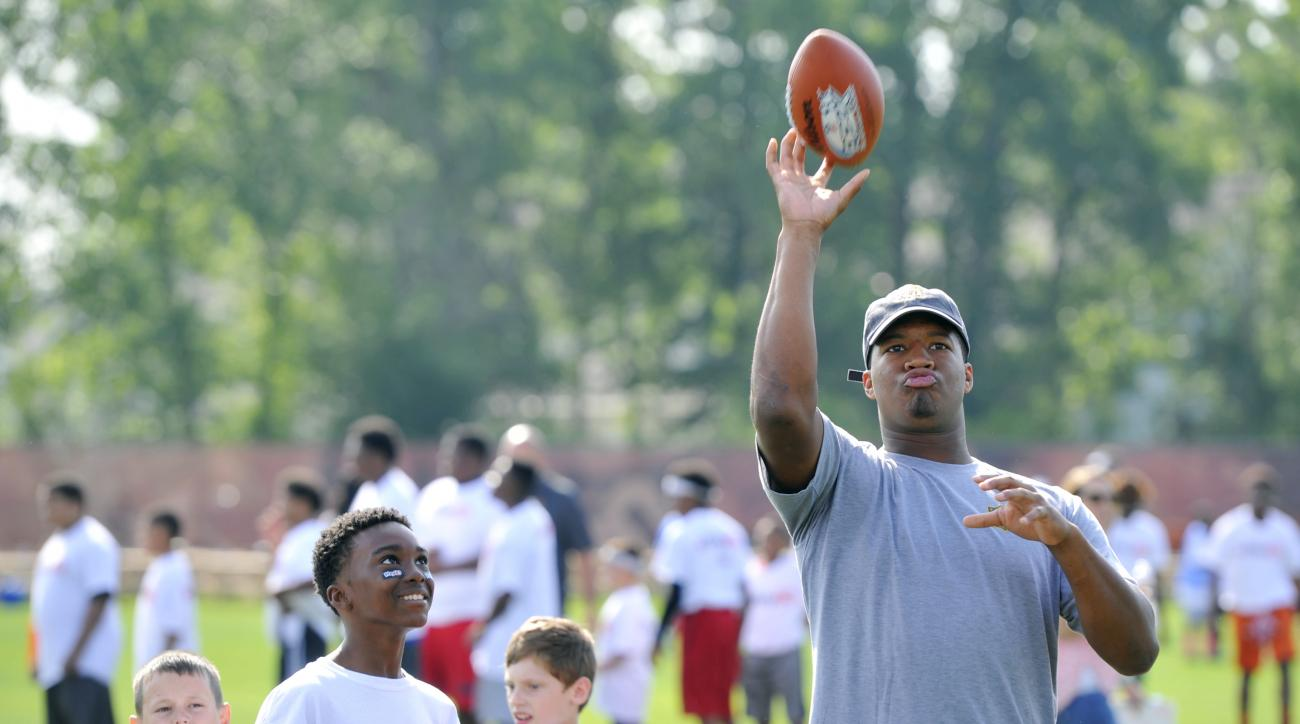 Tampa Bay Buccaneers quarterback Jameis Winston, right, throws a football during a passing drill at the NFL Rookies Symposium in Berea, Ohio, Friday, June 26, 2015. (AP Photo/David Richard)