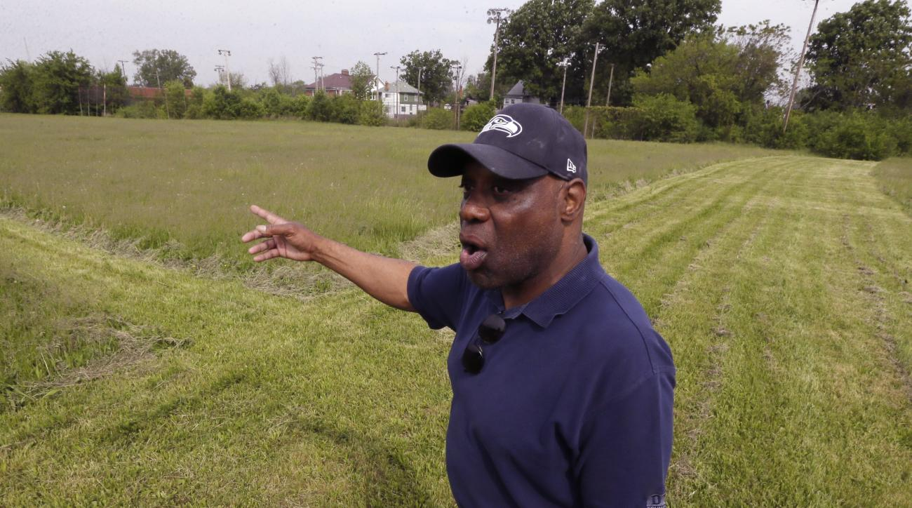 In this photo taken May 29, 2015, former NFL star and Highland Park native Reggie McKenzie stands in the field named in his honor in Highland Park, Mich. McKenzie had to go into his own pocket to have the city-owned field mowed in time for an annual youth