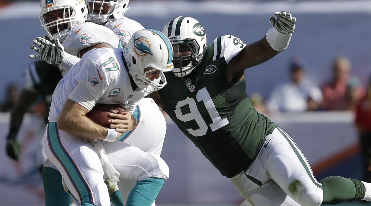 New York Jets defensive end Sheldon Richardson (91) sacks Miami Dolphins quarterback Ryan Tannehill (17) during the first half of an NFL football game, Sunday, Dec. 28, 2014, in Miami Gardens, Fla. (AP Photo/Wilfredo Lee)