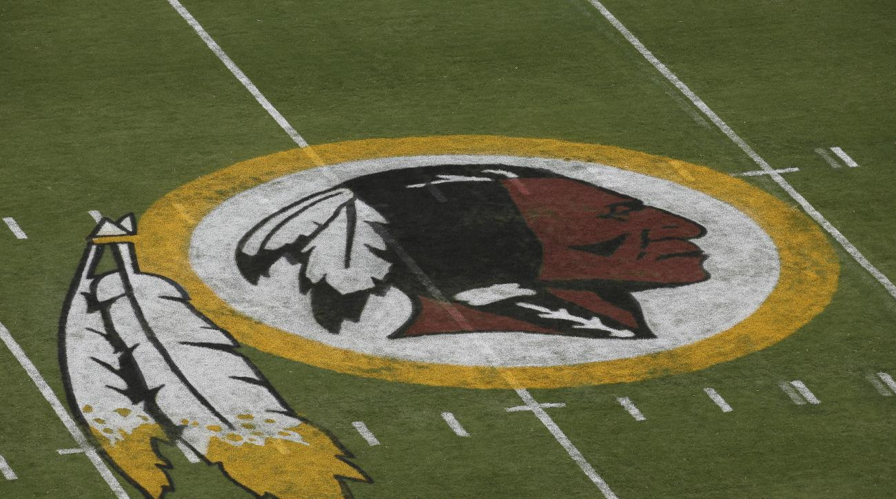 FILE - In this Aug. 7, 2014 file photo, the Washington Redskins logo is seen on the field before an NFL football preseason game against the New England Patriots in Landover, Md.  A federal judge has ordered the Patent and Trademark Office to cancel regist