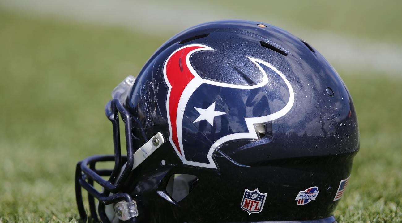 A Houston Texans helmet sits in the grass following a joint practice between the Denver Broncos and the Houston Texans on Wednesday, Aug. 20, 2014, in Englewood, Colo. (AP Photo/Jack Dempsey)