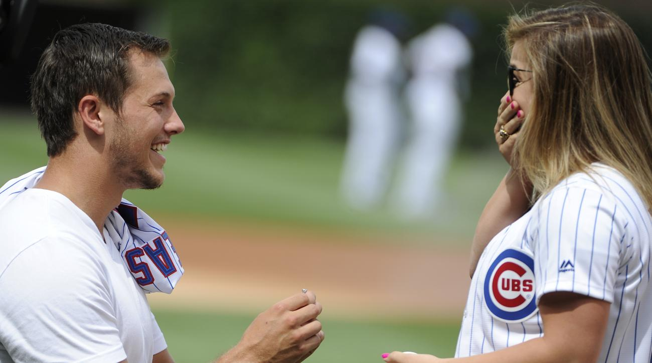Kansas City Chiefs rookie Andrew East, left, proposes to Olympic gold medal gymnast Shawn Johnson before a baseball game between the Chicago Cubs and the Philadelphia Phillies, Friday, July 24, 2015, in Chicago. (AP Photo/David Banks)