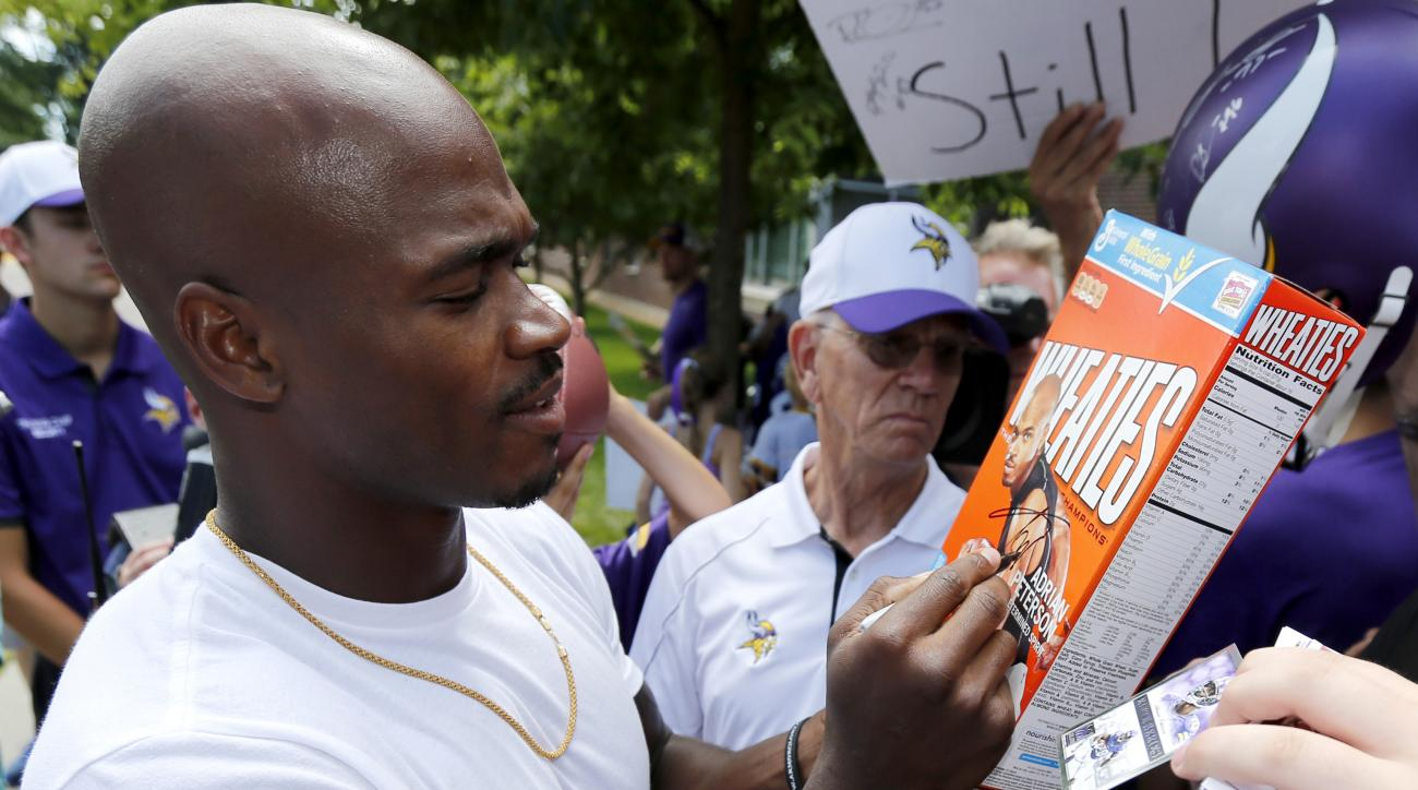 Minnesota Vikings running back Adrian Peterson signs a Wheaties box with his picture on it as he reports to an NFL football training camp at Minnesota State University Saturday, July 25, 2015, in Mankato, Minn. (AP Photo/Charles Rex Arbogast)